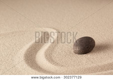 Spa wellness stone therapy background with raked sand. Concept for spiritual healing for body mind and soul. Zen meditation rock.