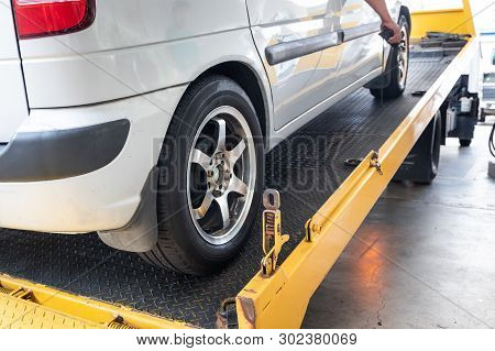 Closeup On Car Towed Onto Flatbed Tow Truck With Cable