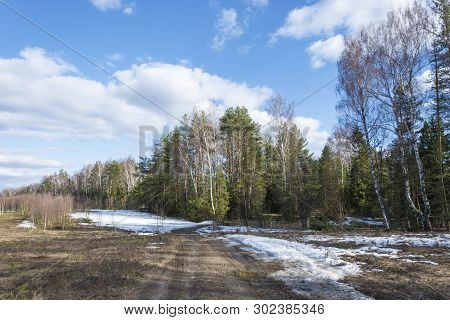 Landscape With A Dirt Road Stretching Into The Spring Forest And A Beautiful Cloudy Sky.