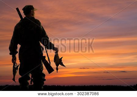 Silhouette Of The Duck Hunter With Prey On The Sunset Background