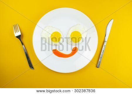 Traditional Breakfast Of Two Fried Eggs. Fun Face From Food. Plate With Eggs On A Yellow Background.