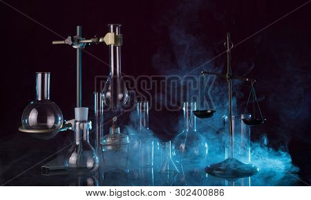 Laboratory Glassware, Chemical Scales, Tripod And A Torch On A Dark Background In The Smoke