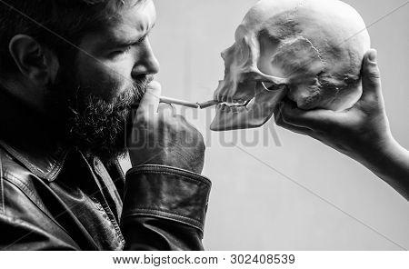 Man Smoking Cigarette Near Human Skull Symbol Of Death. Harmful Habits. Destroy Your Health. Smoking
