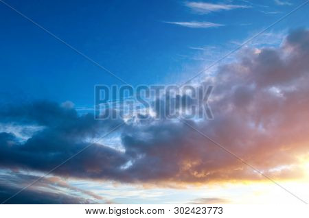Sunset colorful sky background - pink, orange and blue dramatic colorful clouds in the sky lit by evening sunshine. Picturesque sky landscape view