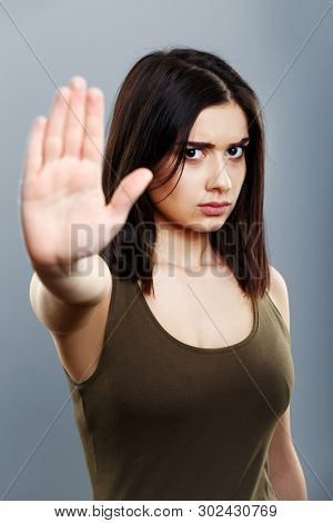 Young woman showing stop hand gesture - isolated on blue gray background
