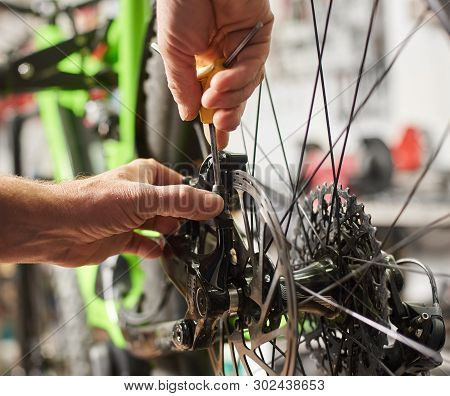Cropped Shot Of Man Mechanic Working In Bicycle Repair Shop, Fixing Mountain Bike Brakes Using Speci