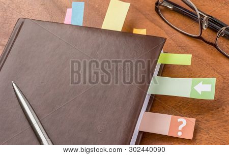 A Daily Planner With Some Sticky Notes