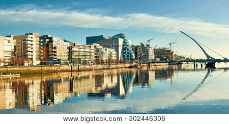 Modern Buildings And Offices On Liffey River In Dublin On A Bright Sunny Day, With Harp Bridge On Th