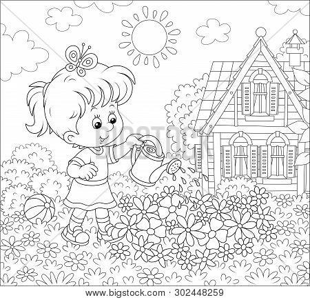 Smiling Little Girl Watering Flowers On A Flowerbed On A Lawn In Front Of Her House On A Sunny Summe