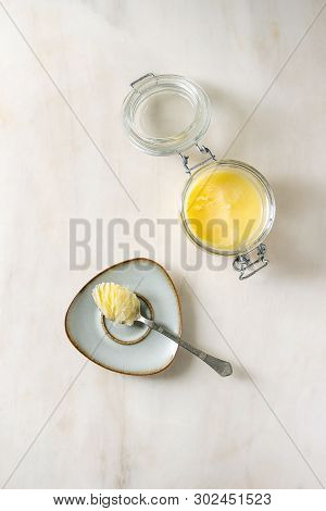Homemade Melted Ghee Clarified Butter In Open Glass Jar And Spoon On Saucer Over White Marble Backgr