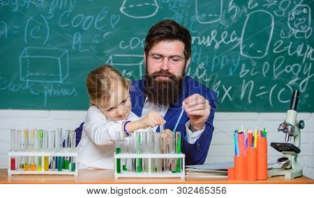Fascinating chemistry lesson. Man bearded teacher and pupil with test tubes in classroom. Private lesson. School chemistry experiment. Explaining chemistry to kid. How to interest children study poster