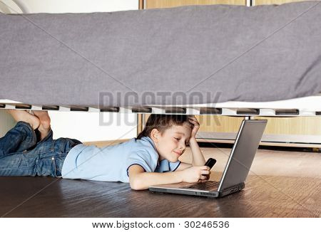 Child with laptop and phone under the bed. Boy playing computer