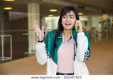Medium shot of pretty young mixed-race woman in green jacket and rose T-shirt talking on phone outside, behaving emotionally, looking surprised. Lifestyle concept poster