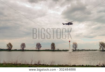 Helicopter Exercises With A Specialized Bucket Suspended On A Cable To Deliver Water For Aerial Fire