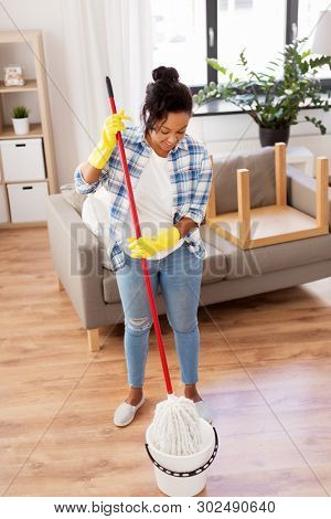 housework and housekeeping concept - african american woman or housewife soaking mop in bucket and cleaning floor at home poster