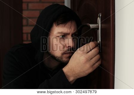 Man Picking Door Lock To Break Into House. Criminal Offence