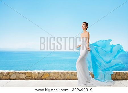 Fashion Model In Summer Dress Over Blue Sea And Sky, Elegant Woman In Long White Gown