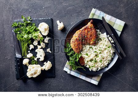 Broiled Chicken Leg Quarter Served With Cauliflower Rice Or Couscous  Served On A Black Plate On A C