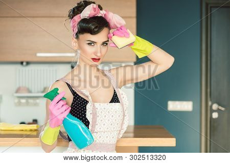 Housewife woman in retro outfit attempting to clean the kitchen wiping sweat from forehead