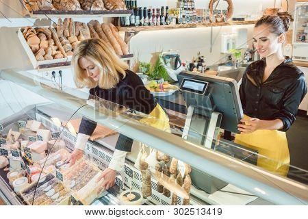 Two friendly saleswomen selling groceries in deli