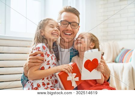 Happy father's day! Children daughters congratulating dad and giving him gift box. Daddy and girls smiling and hugging. Family holiday and togetherness.