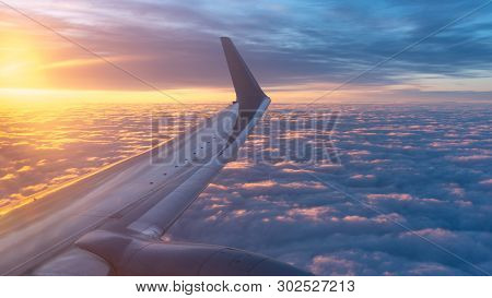 Beautiful Salmon Dawn And The Wing Of An Airplane Above The Clouds. View Of The Dawn In The Clouds F