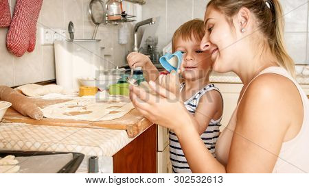 Closeup Portrait Of Young Mother Teaching Her Toddler Son Making Cookies. Child With Parent Baking D