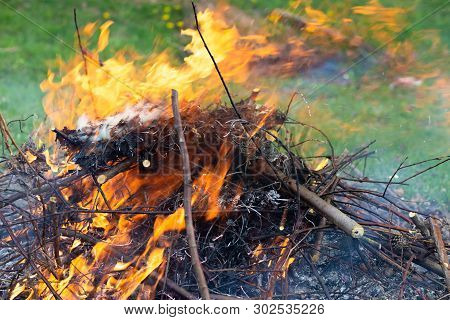 A Large Pile Of Burning Branches And Leaves With Smoke.