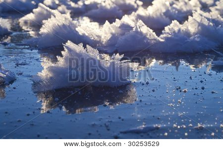 Snow Crystal With Reflection On Blue Ice.