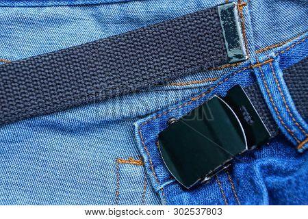 Long Black Belt With A Metal Buckle On A Blue Denim Pants