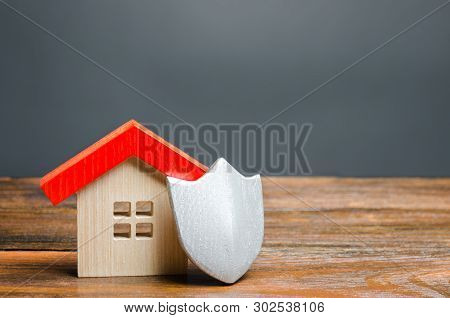 House Figurine And Protective Shield. The Concept Of Home Security And Safety. Alarm Systems. The In