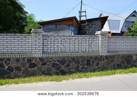 A Long Private Fence Of White Bricks And Gray Stones