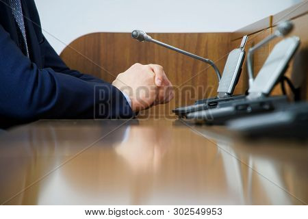 A Businessman Or A Politician In A Suit Sits In Front Of A Microphone While On Duty, Discussing Or M