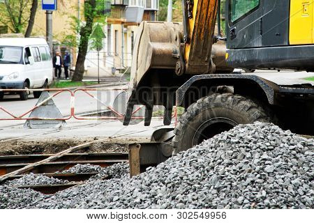 The excavator falls asleep rubble tram rails during the work on their repair and replacement. Roads and urban economy poster