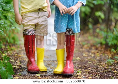 Little Children Wearing Oversized Rubber Boots Holding Hands. Brother And Sister Playing Together. Y