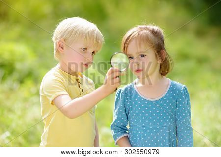 Kids Exploring Nature With Magnifying Glass. Close Up. Little Boy And Girl Looking With Magnifying G
