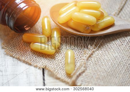 Royal jelly capsules in wooden spoon and sack background / Yellow capsule medicine or supplementary food from nature for health poster
