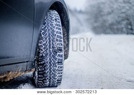 Wheel With Spikes On A Winter Road. Winter Road. Snow Road. Car On The Winter Road. Footprints In Th