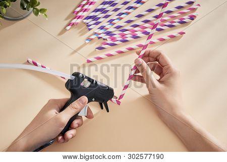 Glue Gun In The Woman's Hand. Woman Glues Straws With A Glue Gun. Closeup