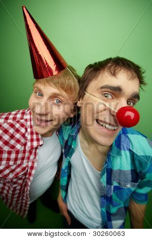 Fools day party in full swing, guys smiling and looking funny, isolated on green background