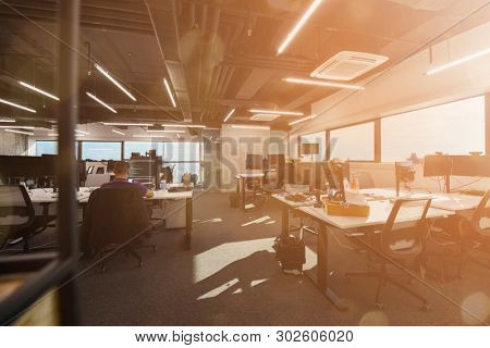 software developers working everyday job writing programming code at modern sunny bright open plan office