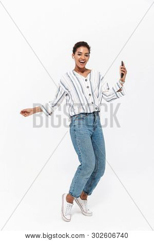 Ful llength portrait of a casual smiling young african woman standing on tiptoes isolated over white background, listening to music with wireless earphones, holding mobile phone