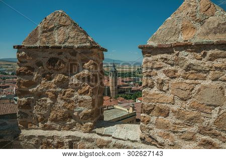 Church Belfry Amid Roofs And Hilly Landscape Seen From Crenel In A Stone Wall Around The Town Of Avi