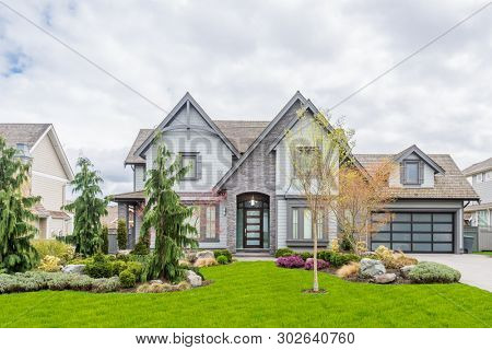 Beautiful exterior of newly built luxury home. Yard with green grass and stones.