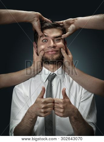 A male model surrounded by hands like his own thoughts on dark background. A young man pretending to be happy and showing the sign of ok. Concept of mental problems, troubles in work, indecision. poster