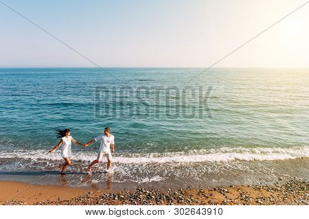 Couple In Love Having Fun On The Beach. Honeymoon Trip. The Couple Are Traveling. Man And Woman On T