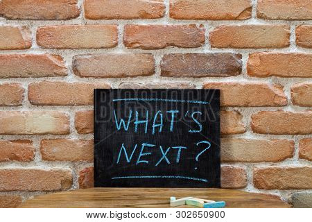 Chalk board with the phrase WHAT'S NEXT? drown by hand and chalks on wooden table on brick wall background. For business presentation.