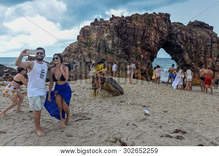 People Taking A Souvenir Photo In Front Of The Natural Arch Of Jericoacoara On Brazil