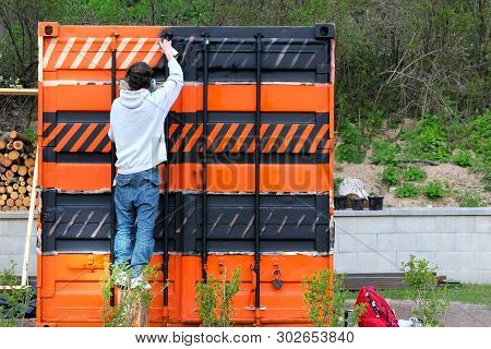 Spray Paint An On The Iron Warehouse Trailer. Young Repairman Is Working With Paint In Spray. Orange