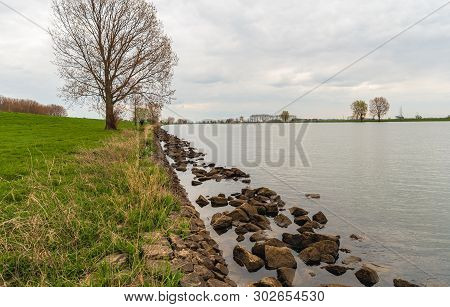Large Stones In The Water Along The Edge Of The River. The Photo Was Taken Of The Dutch River Bergsc